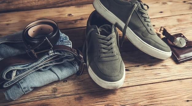 Dżinsy z butami i zegarek z paskiem na stole