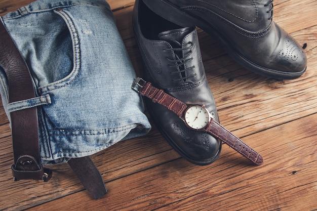 Dżinsy z butami i zegarkiem i paskiem na stole
