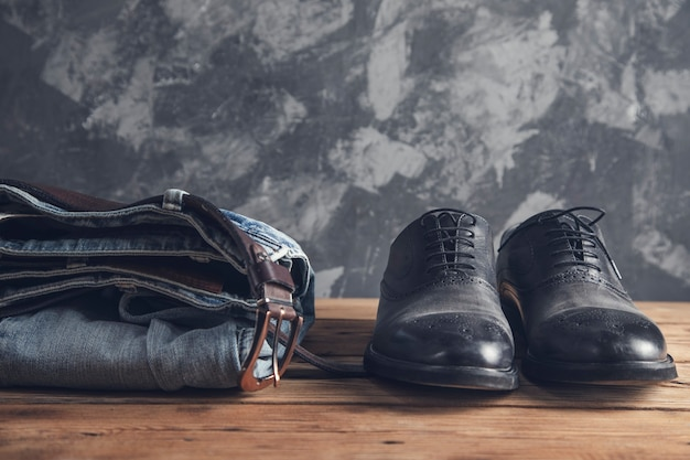 Dżinsy z paskiem i buty na drewnianej ścianie