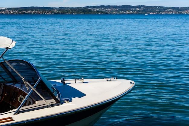 Dziób małej łodzi na błękitnej wodzie jeziora z miejsca na kopię.