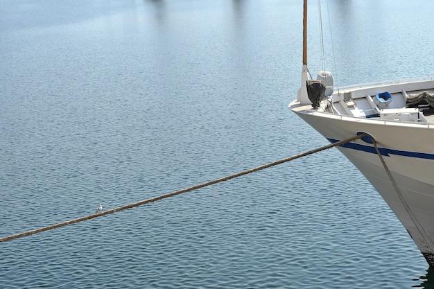 Dziób zacumowanego jachtu z cumą w porcie.