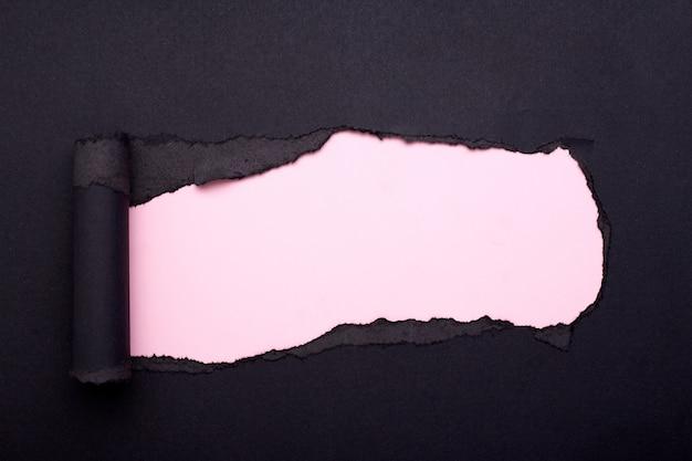 Dziura w czarnym papierze. rozdarty. różowy papier streszczenie