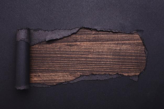 Dziura w czarnym papierze. rozdarty. z drewna . streszczenie