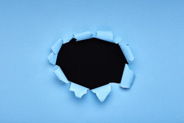 Dziura w niebieskim papierze. rozdarty. czarny drewniany. abstrakcyjny