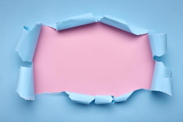 Dziura w niebieskim papierze. rozdarty. różowy streszczenie
