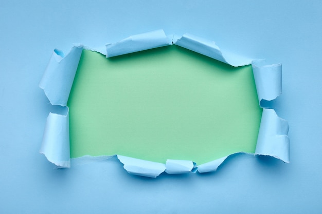 Dziura w niebieskim papierze. rozdarty. zielony . streszczenie