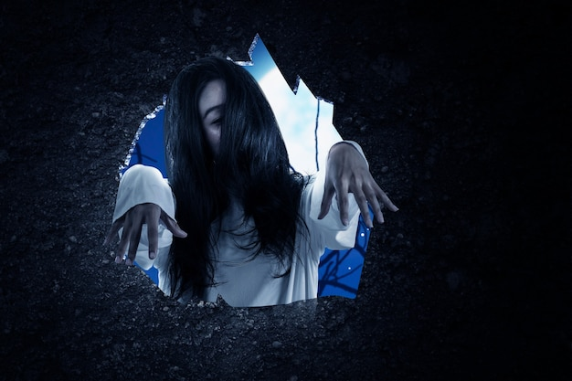 Dziura w ścianie z przerażającą kobietą-duchem stojącą na tle sceny nocnej. koncepcja halloween