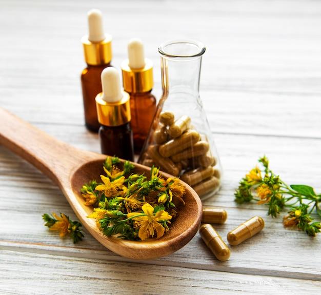 Dziurawiec, ziołowe tabletki medyczne w probówce, butelki z naturalnym olejem na stole