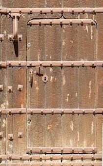 Dziurka w starych drewnianych drzwiach z boazerią z antykami