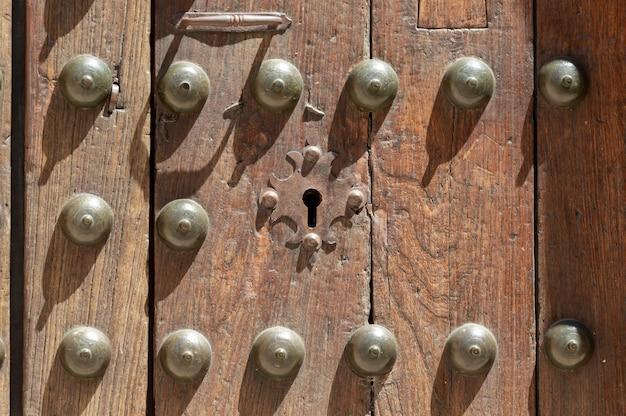 Dziurka w starych drewnianych panelach z antyczną klamką; zardzewiały i wyblakły
