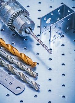 Dziurkujący kątów skrętów metalu władcy świder i kawałki na kruszcowym tło budowy pojęciu