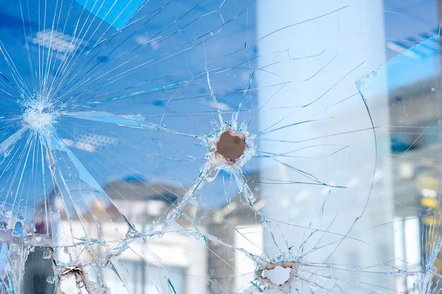 Dziury po kulach w oknie sklepu
