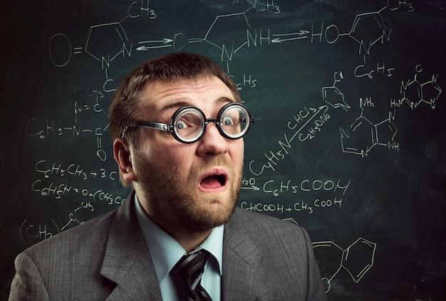 Dziwaczny profesor w okularach zastanawiający się nad wzorami chemicznymi na tablicy