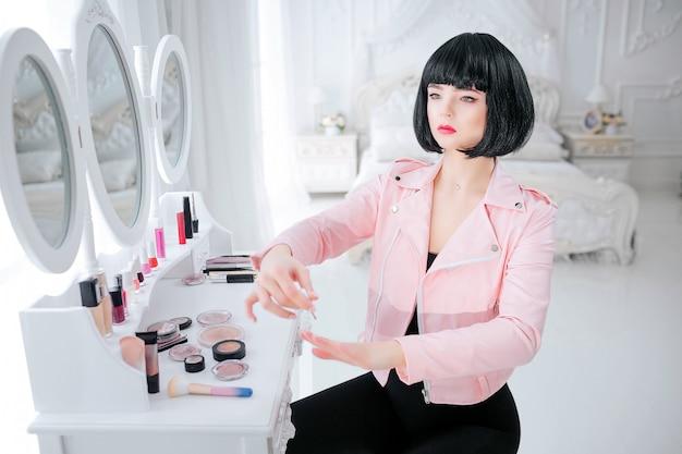 Dziwak mody. urocza syntetyczna dziewczyna, sztuczna lalka o pustym wyglądzie i krótkich czarnych włosach maluje paznokcie siedząc przy lustrze. stylowa kobieta w różowej kurtce w sypialni. moda i uroda