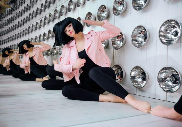 Dziwak mody. w studiu siedzi syntetyczna dziewczyna glamour, sztuczna lalka o pustym wyglądzie i krótkie czarne włosy. stylowa piękna kobieta w różowej kurtce w pobliżu żarówek. koncepcja mody i urody