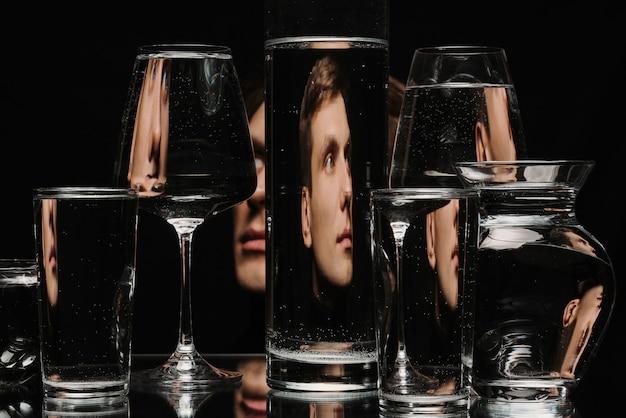 Dziwny abstrakcyjny portret mężczyzny przez szybę zbiornika z wodą z odbiciami i zniekształceniami