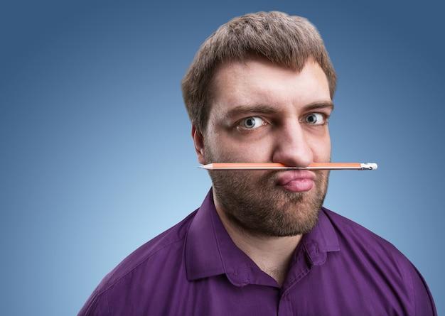 Dziwny mężczyzna trzyma ołówek w nosie i ustach