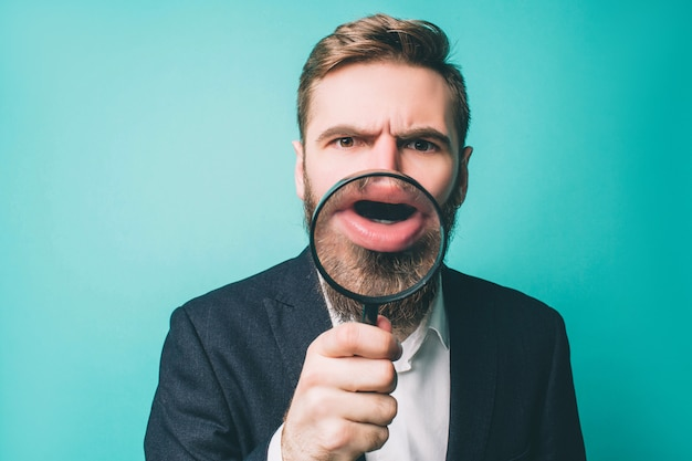 Dziwny mężczyzna w apartamencie stoi i pokazuje usta przez szkło powiększające