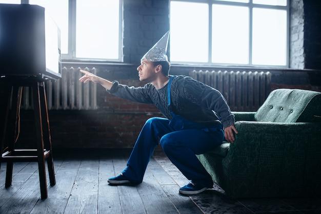 Dziwny mężczyzna w czapce z folii aluminiowej sięga do telewizora, koncepcja paranoi. ufo, teoria spiskowa, ochrona przed kradzieżą mózgu, fobia