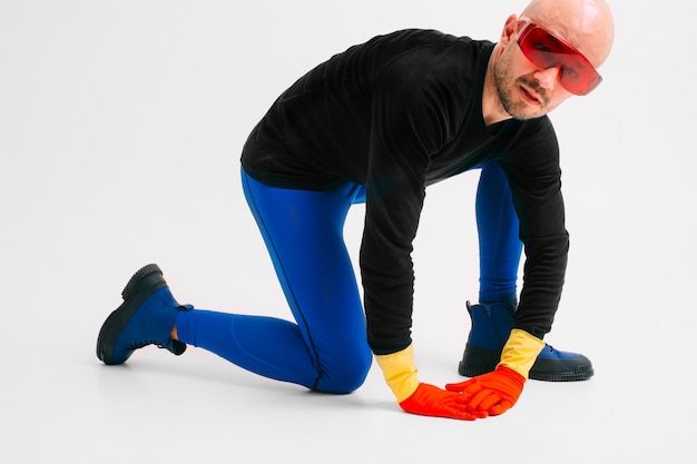 Dziwny mężczyzna w czerwonych żółtych gumowych rękawiczkach w futurystycznych okularach i rajstopach z pozowaniem w białym studiu