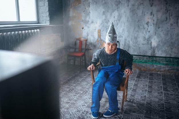 Dziwny mężczyzna w kasku z folii aluminiowej, oglądający telewizję, ochrona umysłu, koncepcja paranoi. ufo, teoria spiskowa, fobia telepatyczna