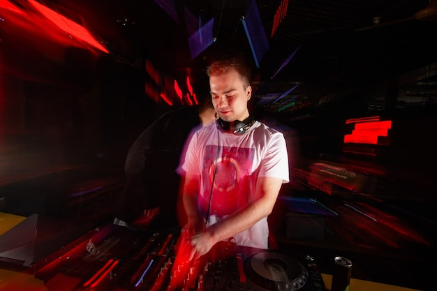 Dżokej napędza tłum. niewyraźny mężczyzna w białej koszulce i słuchawkach miksuje utwory z gramofonami. rave w klubie nocnym. koncepcja życia nocnego. niewyraźne wnętrze klubu z czerwonymi światłami.