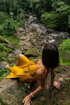 Dźwięki rzeki. atrakcyjna osoba płci żeńskiej, oparta na kamieniu, z niecierpliwością czekającą na płynącą górską rzekę