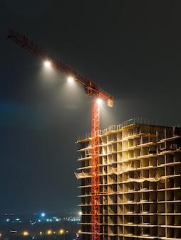 Dźwig budowlany i niedokończony budynek w nocy. jasne światła zamontowane na dźwigu.