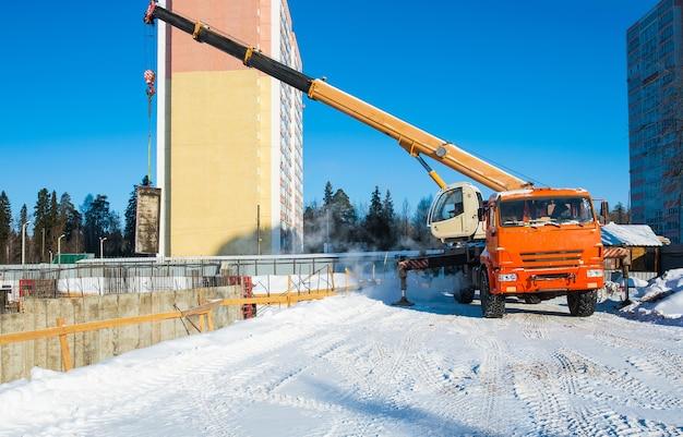 Dźwig budowlany pracuje na placu budowy z ładunkiem