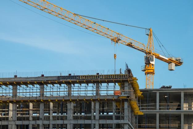 Dźwig budowlany w pobliżu nowo wybudowanego domu. budowa i wywołanie zdjęcia poziomego