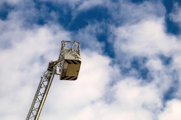 Dźwig z koszem. drabina strażacka z niebieskim niebem i chmurami. biała drabina ratunkowa