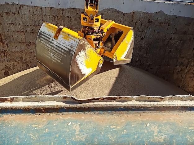 Dźwig z łyżką manipulatora ładuje pszenicę na statek do przewozu ładunków suchych przy nabrzeżu w porcie