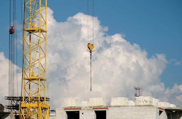 Dźwigi budowlane i budowa domu przeciw błękitne niebo