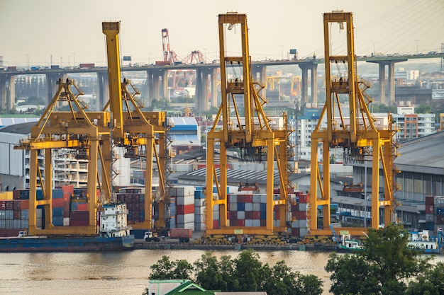 Dźwigi i przemysłowe statki towarowe w porcie o zmierzchu.