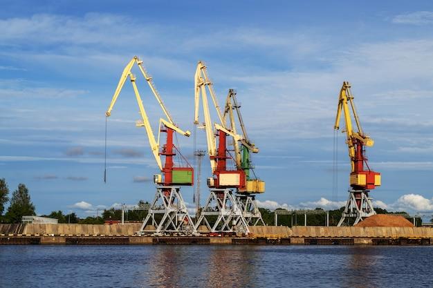 Dźwigi towarowe w terminalu w porcie statków rzecznych w ventspils, łotwa, morze bałtyckie. import wysyłkowy lub