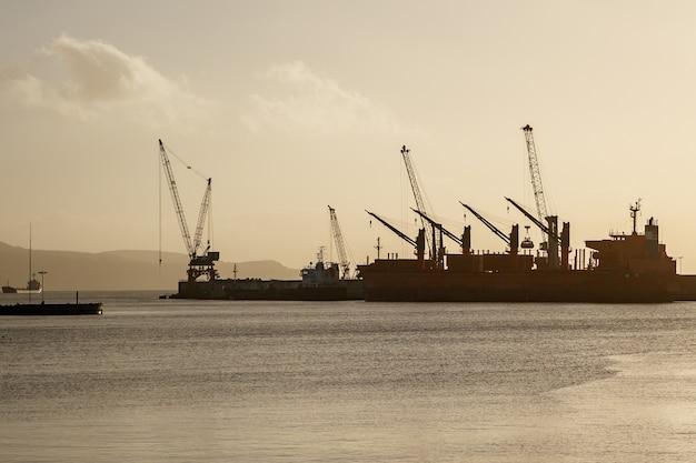 Dźwigi w porcie, centrum logistyczne na morzu, zachód słońca