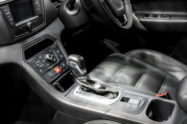 Dźwignia zmiany biegów lub dźwignia zmiany biegów z uchwytem na kubek i klimatyzacją w nowoczesnym samochodzie.