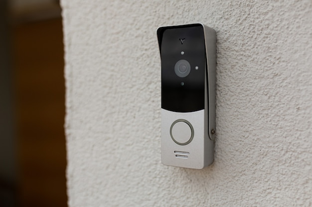 Dzwonek na ścianie domu z kamerą monitorującą