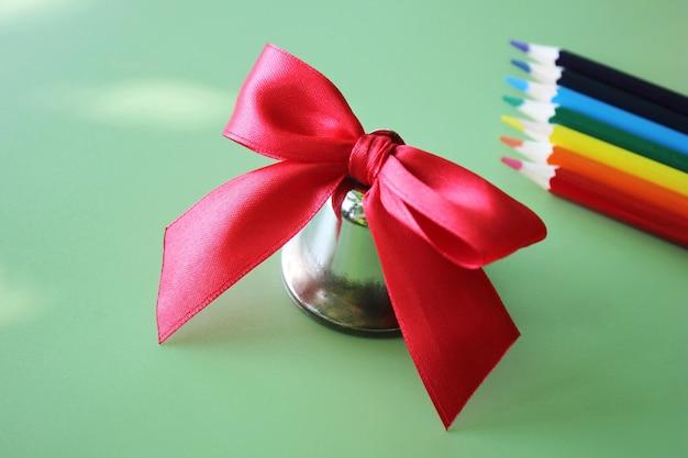 Dzwonek szkolny z czerwoną kokardą i kolorowymi ołówkami z tyłu na miętowym tle