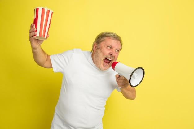 Dzwoni z spokojem ust, trzyma popcorn. portret mężczyzny kaukaski na żółtym tle studio. piękny model męski w białej koszuli.