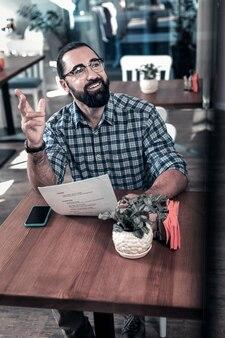 Dzwonię do kelnera. rozpromieniony ciemnowłosy mężczyzna w okularach unoszący rękę wzywając kelnera po wybraniu dania