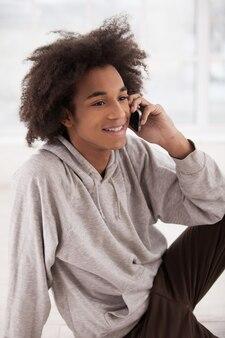 Dzwonię do przyjaciół. wesoła afrykańska nastolatka rozmawiająca przez telefon komórkowy i uśmiechnięta