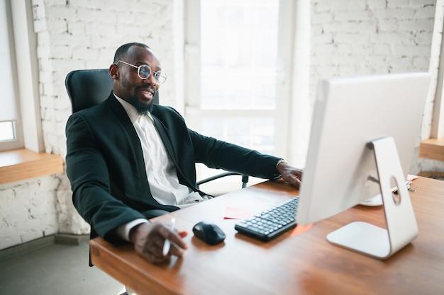 Dzwonię, rozmawiam przez telefon. afro-przedsiębiorca, biznesmen pracujący skoncentrowany w biurze. wygląda serio, zajęty, w klasycznym garniturze. pojęcie pracy, finansów, biznesu, sukcesu, przywództwa.