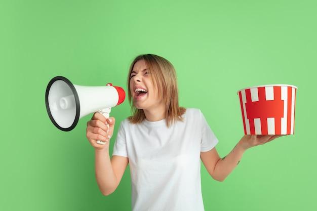 Dzwonię, trzymam popcorn. kaukaski portret młodej kobiety na zielonej ścianie studia