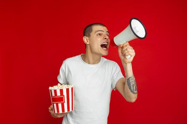 Dzwonię z głośnikiem. kaukaski portret młodego mężczyzny na czerwonej ścianie. piękny męski model z popcornem.