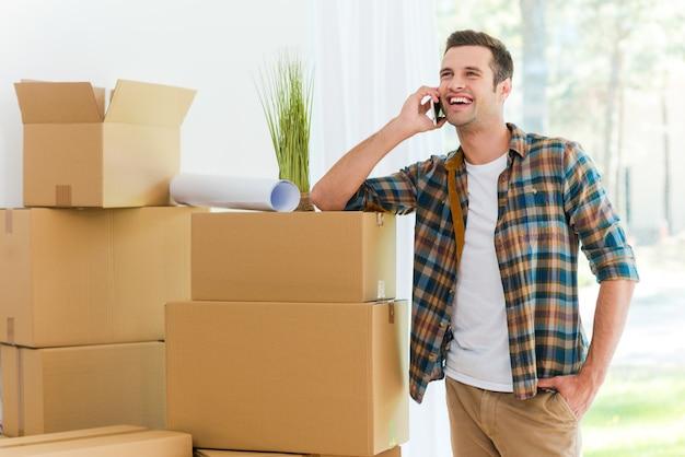 Dzwonię ze swojego nowego mieszkania. wesoły młody człowiek rozmawia przez telefon komórkowy, opierając się o kartonowe pudełko