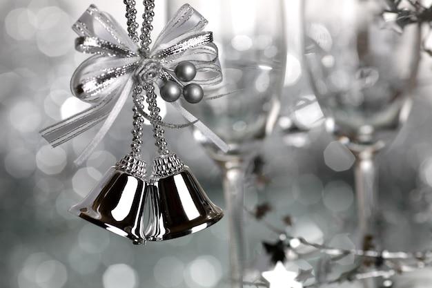 Dzwonki bożonarodzeniowe i dwa puste kieliszki do wina na srebrnym tle - płytka głębia ostrości