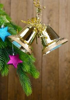 Dzwonki z dekoracją świąteczną na drewnianym tle
