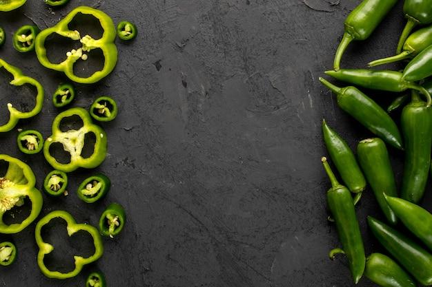 Dzwonkowego pieprzu zieleni świeży pokrojony i korzenny zielony pieprz na szarym tle