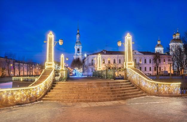 Dzwonnica katedry św. mikołaja w sankt petersburgu i most krasnogvardeisky pod błękitnym nocnym niebem